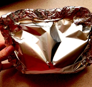 Take edges of the tinfoil to form a squared pocket and fold the edges to seal them.